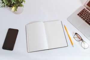 white open book on a white desk with laptop